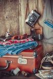 Gammal resväska, gymnastikskor, kläder, solglasögon, översikter, filmer arkivbilder