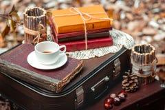 Gammal resväska med gamla böcker och kopp te Arkivbild