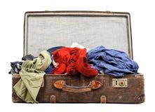 Gammal resväska mycket av kläder arkivbild