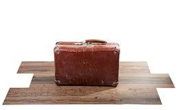 Gammal resväska på trägolv Arkivfoto