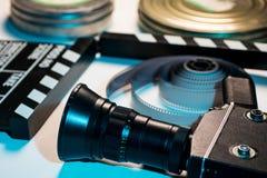 Gammal retro kamera, filmclapper, rullar av filmen och en 35mm askfil Royaltyfri Fotografi