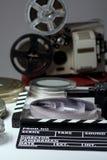 Gammal retro kamera, filmclapper, rullar av filmen och 35mm askar f Royaltyfri Bild