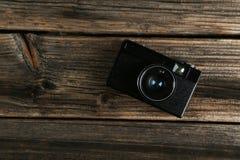 Gammal retro kamera på brun träbakgrund Arkivbilder