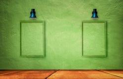 Gammal retro lamp- och fotoram på den gröna grungebetongväggen arkivfoto