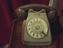 Gammal retro telefon på en trätabell med den röda gardinen på bakgrunden - gammalt foto, tappningstileffekt fotografering för bildbyråer