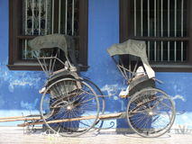 Gammal Rickshaw förutom den blåa herrgården i Georgetown, Malaysia Arkivfoton