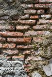 Gammal riden ut murverkvägg med att smula tegelsten och många cementlappar, som en texturerad bakgrund fotografering för bildbyråer