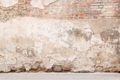 Gammal riden ut tappningtegelstenvägg med bruten murbruk och trottoar på jordningen grungy stads- för bakgrund Arkivbild