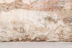 Gammal riden ut tappningtegelstenvägg med bruten murbruk och trottoar på jordningen grungy stads- för bakgrund Royaltyfri Foto
