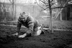 Gammal romanian man som arbetar hans land i en traditionell väg med tomma händer arkivfoton