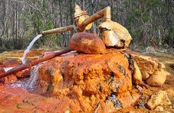 Gammal rostad källa av mineralvatten som innehåller järn arkivfoto