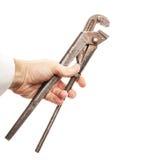 Gammal rostad skruvskiftnyckel i den manliga handen som isoleras på vit Arkivfoto