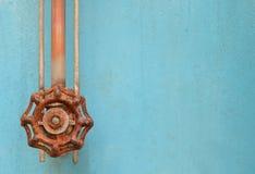 Gammal rostad ventil på blå Grungemetall arkivfoto