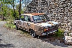 Gammal rostig bil i kroatisk by arkivfoton
