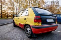 Gammal rostig bil med färgglade karosseripaneler och eftersatt underhåll arkivbilder