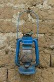 Gammal rostig blå oljalykta på en gyttjategelstenvägg royaltyfri fotografi