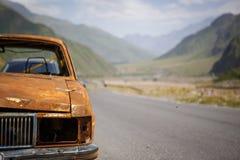 Gammal rostig bränd bil på vägrenen av Georgia som omges av berg och skönhet royaltyfria bilder