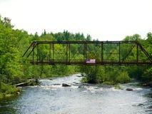 Gammal rostig bro med USA flaggan royaltyfri fotografi