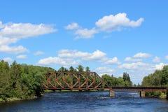 Gammal rostig bro som spänner över över en flod Royaltyfri Fotografi