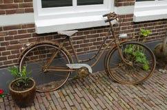 Gammal rostig cykel mot en egenskap i Nederländerna Royaltyfri Fotografi
