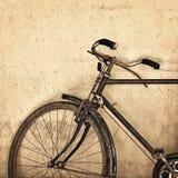 Gammal rostig cykel på grungeväggbakgrund Royaltyfri Fotografi