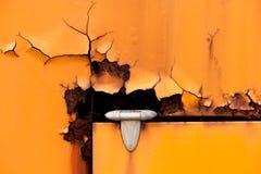 Gammal rostig gångjärndetalj av den orange metalldörren Fotografering för Bildbyråer