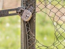 Gammal rostig hänglås och ett brutet staket royaltyfria foton