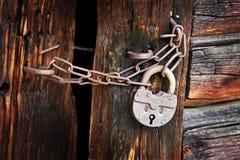 Gammal rostig hänglås på den lantliga träporten Arkivfoton
