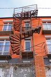 Gammal rostig järnspiraltrappuppgång på ett ljust orange höghus arkivfoto