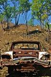 Gammal rostig klassisk bil som ser den ilskna vridna stötdämparen i buske Royaltyfria Bilder