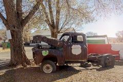 Gammal rostig lastbil under ett träd fotografering för bildbyråer