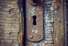Gammal rostig nyckelhål i den gamla trädörren royaltyfri fotografi