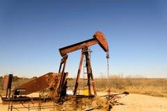 Gammal rostig olje- borrtorn i solljus med blå himmel Royaltyfri Fotografi