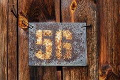 Gammal rostig platta med husnummer Arkivfoto