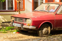 Gammal, rostig röd Dacia bil 1300, med ett plant gummihjul men aktiva registreringsskyltar som parkeras i solen arkivfoto