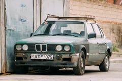 Gammal rostig sedanbil BMW 3 serie, E30 som parkerar på gatan BMW Royaltyfri Bild