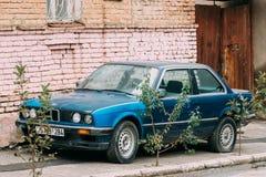 Gammal rostig sedanbil BMW 3 serie, E30 som parkerar på gatan BMW Arkivbilder