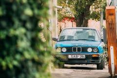 Gammal rostig sedanbil BMW 3 serie, E30 som parkerar på gatan BMW Arkivfoto