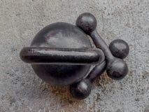 Gammal rostig svart kettlebell och två lilla hantlar på noncrete f Royaltyfri Bild