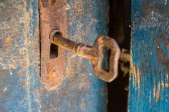 Gammal rostig tangent och nyckelhål på en blå trädörr royaltyfria foton