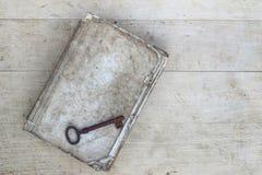 Gammal rostig tangent på den sönderrivna boken Fotografering för Bildbyråer