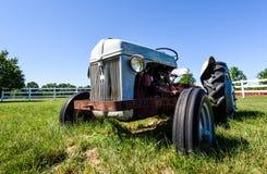 Gammal rostig traktor i ett fält Royaltyfri Bild