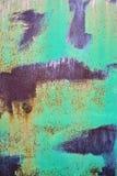 Gammal rostig yttersida som målas med sjaskig målarfärg för turkos, vertikal grungebakgrund royaltyfri foto