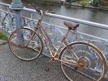 Gammal rostiga dams cykel som parkeras på en broräcke och glömms därefter arkivfoto