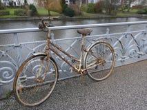 Gammal rostiga dams cykel som parkeras på en broräcke och glömms därefter royaltyfri fotografi