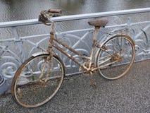 Gammal rostiga dams cykel som parkeras på en broräcke och glömms därefter royaltyfria foton