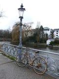 Gammal rostiga dams cykel som parkeras på en broräcke och glömms därefter royaltyfria bilder