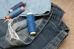 Gammal sönderriven jeans på en bakgrund av säckväv Fotografering för Bildbyråer