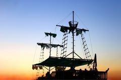 Gammal sailer piratkopierar skeppet, med sönderrivet seglar, på solnedgången arkivbild