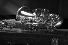 Gammal saxofon som ligger på resväskan Arkivfoton